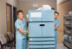 Nurses Pushing Trolley Filled With Linen In. Female and male nurses pushing trolley filled with linen in hospital hallway Stock Image