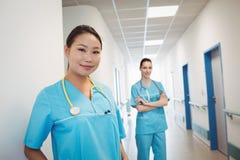 Nurses standing in hospital corridor. Portrait of nurses standing in hospital corridor stock photos