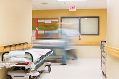 Nurses With Stretcher Walking In Hospital Corridor Stock Photos