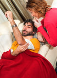 NurseTending to her Injured Man Stock Image