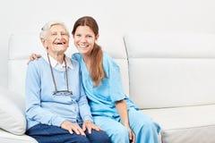 Nursing assistance and laughing happy senior citizen. Smiling nursing assistant and laughing happy senior women on the sofa stock photos