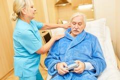 Nursing assistance looks after a sick senior. Nurse or nursing assistant looks after a sick senior citizen in a nursing home stock image