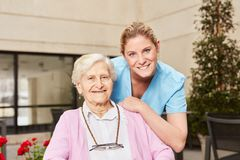 Nursing assistance and senior woman together. Nursing assistance and senior women together in nursing home or senior residence royalty free stock images