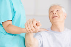 Nursing assistant holding hand of senior man Stock Image