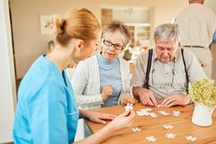 Nursing home helps seniors to play puzzle. Nursing home helps a senior couple to play jigsaw puzzles at home or at home stock photos