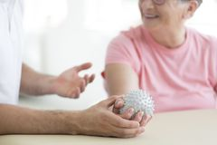 Pnf exercises with spiked ball. Nursing home patient doing active pnf exercises with a grey spiked ball used for rehabilitation purposes Royalty Free Stock Photo