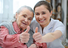 Nursing home. Senior women and female nurse are showing thumbs up Royalty Free Stock Images