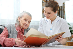 Nursing home. Senior women and nurse looking together at album with old photographs Royalty Free Stock Photos