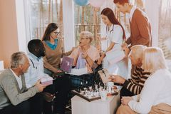 Nursing Home. Very Happy Young and Old People. Old Woman Very Surprised. Birthday Party Celebration. Madly Happy Retiree in Wheelchair. Guests Give Gifts to stock photo