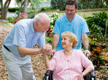 Nursing Home Visit. Senior husband visiting his disabled wife on the grounds of the nursing home while a nurse pushes her wheelchair Royalty Free Stock Photography