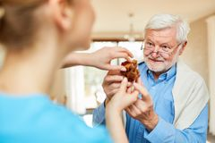 Nursing lady looks after senior man with dementia. Nursing lady looks after senior men with dementia while playing with the wooden puzzle royalty free stock photos