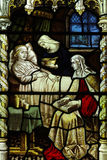 Nursing a sick person in stained glass Royalty Free Stock Image