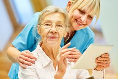 Nursing support senior woman with the tablet royalty free stock photography
