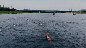 NurSultan_Kazahstan_-_June_17_2018_Ironman 70 30 Tiro aéreo dos triathletes na água aberta Movimentos da câmera acima dos nadador vídeos de arquivo