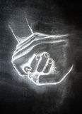 Nurturing hands. White chalk on a blackboard of nurturing hands holding and helping another Stock Photography