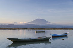 Nusa lembongan and gunung agung volcano. Seaweed collectors and boats on the beaches of nusa lembongan island indonesia with balis gunung agung volcano, towering Royalty Free Stock Images
