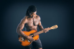 Nuscular topless young black man playing guitar. Portrait of muscular topless young black man playing guitar on dark background Stock Photos