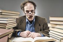 Nussartiger Professor zwischen einem Stapel Büchern Lizenzfreies Stockfoto