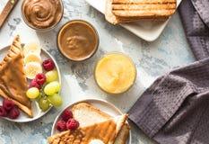 Nussbutter und -brot rösten auf weißer Platte Sortierte Nussbutter verbreitete auf weißem Toastbrot Gesunde Ernährung, strenger V stockfotografie