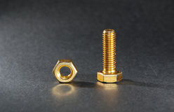 Nut and bolt. The golden nut and bolt in the black background Royalty Free Stock Image