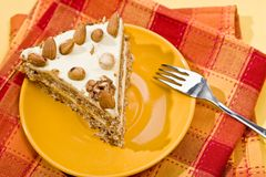 Nut cake. Cake with almonds and nut on the yellow plate Stock Image