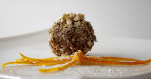 Nut covered chocolate ball. Closeup of nut covered chocolate ball with orange decoration in the foreground Stock Photos