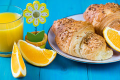 Nut croissants and orange juice with orange slices. On a vibrant blue wooden background Stock Photos