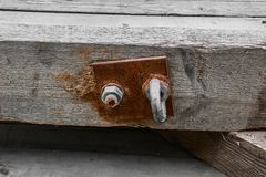 The nut fastens a metal rusty plate with a loop to a wooden bar stock photography