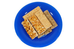 Nut-and-honey bar. On blue plate, isolated Stock Images