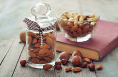 Nut mix in glass bowls. Almonds, walnuts, cashew and hazelnuts in glass bowls on wooden background Royalty Free Stock Photos