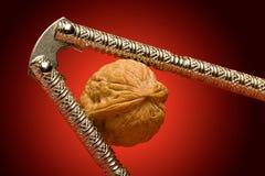 Nut and Nutcracker. A walnut in a decorative nutcracker against a red spotlit background Stock Photos