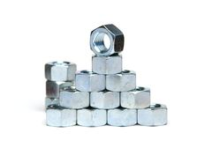 Nut Pyramid. A pyramid of large steel nuts with a single nut topper Stock Photos