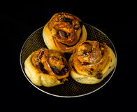 Nut rolls on a plate with black background. Raisinsrolls and nuts on a plate isolated on black Stock Photography