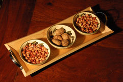 Nut selection. Nuts of differing sorts in bowls on wood tray on red wooden table Stock Photo