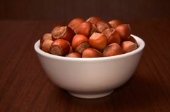 A nut in a white bowl against the background of a dark tree. Sid. A nut in a white bowl against the background of a dark tree Royalty Free Stock Photography