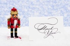 Nutcracker. Sitting on snow with thank you card on a snowflake background stock photography