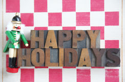 Nutcracker checkerboard happy holidays. A nutcracker with the words 'happy holidays' in wood type on a stenciled checkerboard Stock Photos