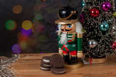 Nutcracker dressed in uniform guard the cookies for Santa Claus Royalty Free Stock Photography