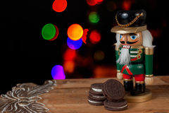 Nutcracker dressed in uniform guard the cookies for Santa Claus Royalty Free Stock Images