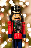 Nutcracker in Front of a Christmas Tree. A shiny wooden nutcracker stands in front of an out of focus Christmas tree Stock Photos