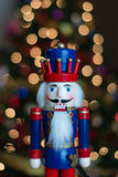 Nutcracker in Front of a Christmas Tree. This is a colorful nutcracker in front of a Christmas tree Stock Photo