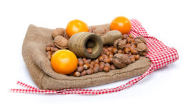 A nutcracker, hazelnuts, mandarins and walnuts on a burlap bag Stock Photo