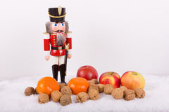 Nutcracker with nuts, tangerines at Christmas time Stock Photography