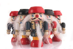 Nutcracker parade. Little wooden nutcrackers in a fanlike parade, isolated white background stock image