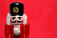 Nutcracker on red. Close-up of a Christmas nutcracker on a red background with room for text Stock Photography