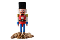 Nutcracker soldier with pile of nuts. Nutcracker soldier,red,blue and black hat .isolated on white background with a pile of nuts Royalty Free Stock Image