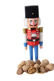 Nutcracker soldier with a pile of walnuts. Nutcracker soldier,red,blue and black hat .isolated on white background with a pile of nuts Royalty Free Stock Images