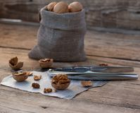 Nutcracker with walnuts on wooden background. Nutcracker with walnuts in canvas sack and nutshell on scrap of newspaper on wooden background Royalty Free Stock Photo