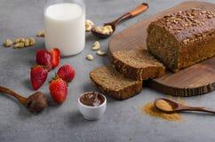 Nutella die met wholegrain brood wordt uitgespreid Stock Afbeelding