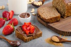 Nutella die met wholegrain brood wordt uitgespreid Royalty-vrije Stock Afbeelding